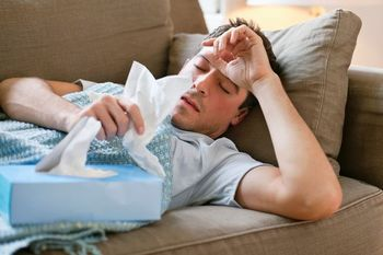 PROD-Man-with-a-cold-lying-in-sofa-holding-tissues.jpg
